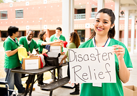 Woman standing outside holding a Disaster Relief sign