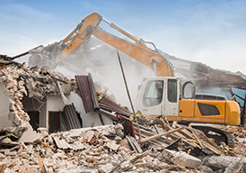 Heavy equipment demolishing a structure