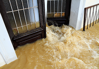 Muddy floodwaters rushing through an open door