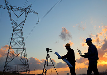 Utility surveyors standing under power lines