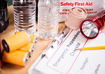 Emergency supplies - water, batteries, bandage, and checklist on a table