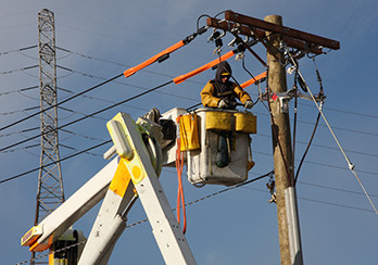 Utility worker in a bucket making repairs to a wooden utility pole