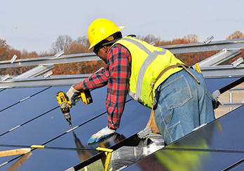 Worker in a hard hat using a tool to install solar panels