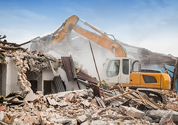 Construction equipment on pile of rubble demolishing house