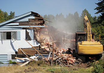 Construction equipment demolishing house