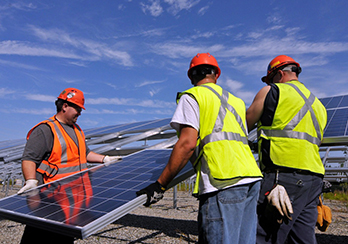 Three workers in hard hats and safety vests installing solar panels