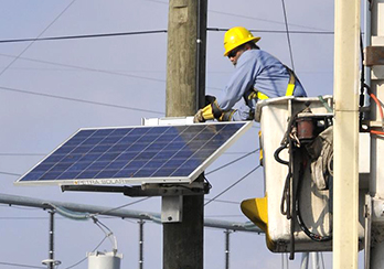 Worker in elevated lift bucket installing solar panel onto a utility pole