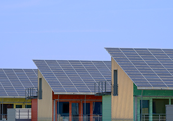 Solar panels installed on a series of buildings with slanted roofs