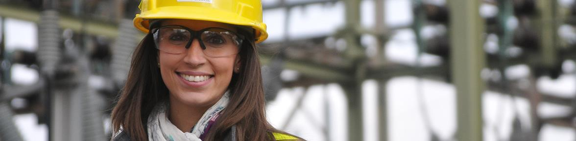 A female PSE&G executive wearing a hard hat in front of a power station