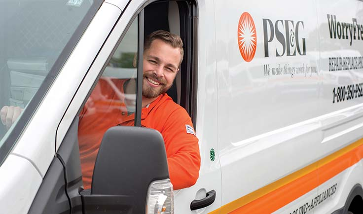 PSE&G technician leaning out of a truck window and smiling