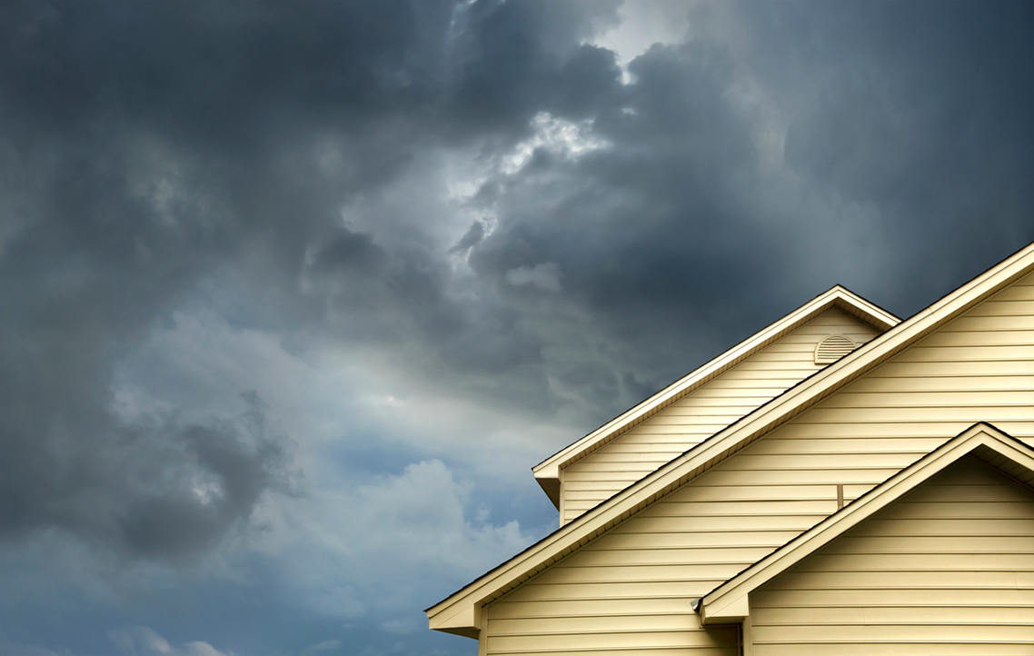 A house rooftop and a stormy sky