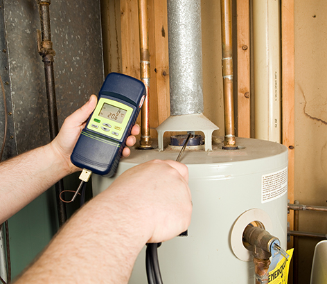 Technician holding a monitoring device next to a water heater