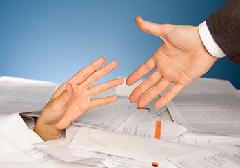 One hand reaching to help another hand that is buried in paperwork