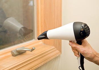 Hand holding hairdryer up against weather stripping on a window