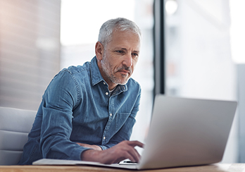 Older man sitting at a table, looking at a laptop