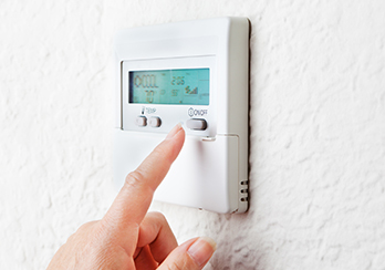 Finger touching programmable thermostat