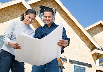 Man and woman standing outside a house, looking at blueprints