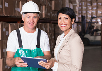 Man wearing hardhat and woman standing in a partially-constructed building