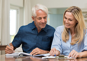 Older man with an open book and younger woman with a clipboard sitting at a table, looking at papers