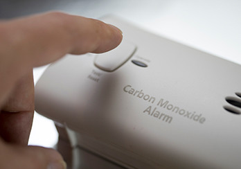 A finger about to depress the test button on a carbon monoxide detector