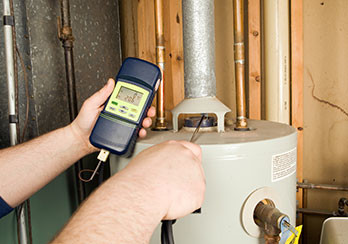 A technician using a device to test for carbon monoxide leaks