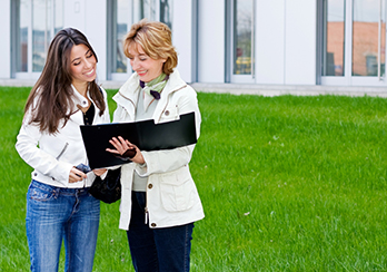 Two women standing on grass in front of a building, looking at a black folder
