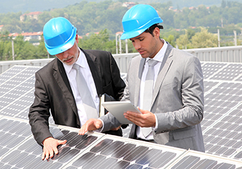 Two men in suits and hardhats consulting plans and looking at solar panels