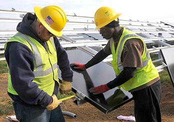 Two workers assembling solar modules