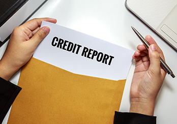 Hands holding a paper titled Credit Report