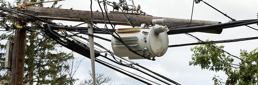 Snapped utility pole and transformer lying across wires