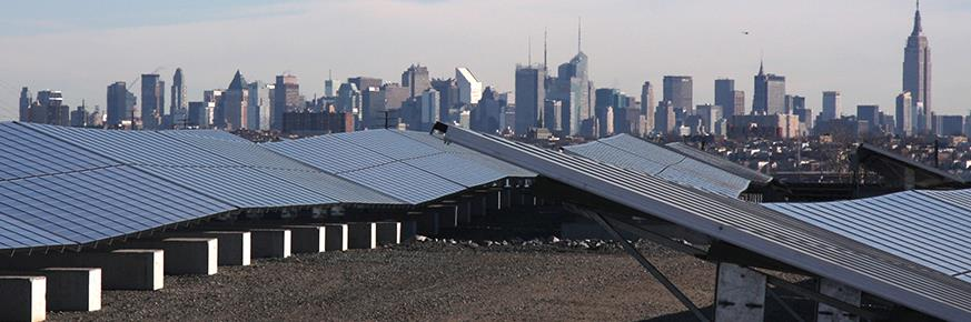 Two rows of solar panels on a New Jersey rooftop with the New York City skyline in the background