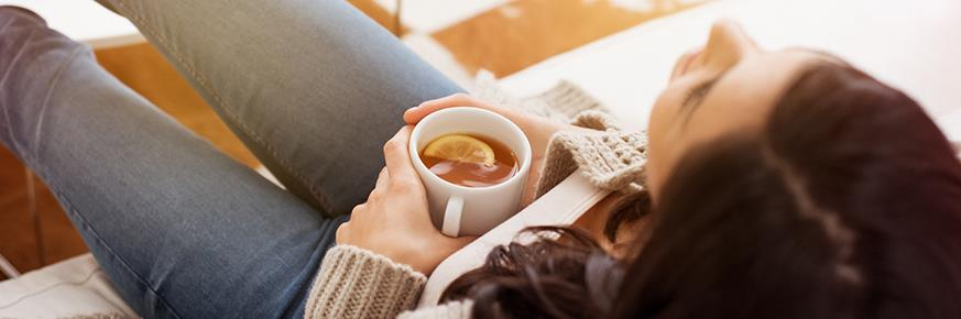 Woman at home wearing a sweater lounging comfortably on a couch drinking hot tea with lemon.