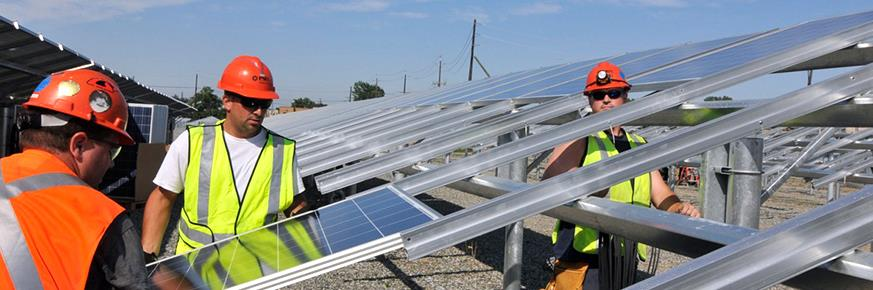 Two workers installing solar panels onto an elevated grid