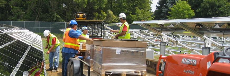 Work crew unloading solar panels from utility vehicle