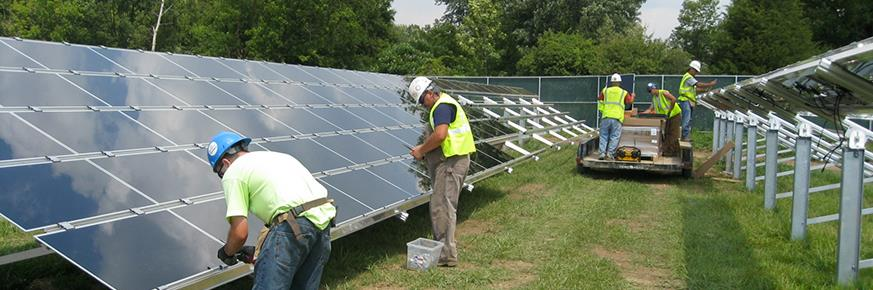 A group of workers in a filed installing solar panels as a photovoltaic array