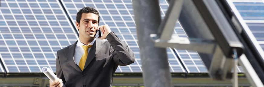 Man in suit with cellphone in front of solar panels
